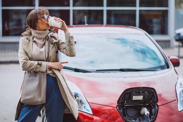 Женщина заряжает электро автомобиль на электрической заправке и пьет кофе Бесплатные Фотографии