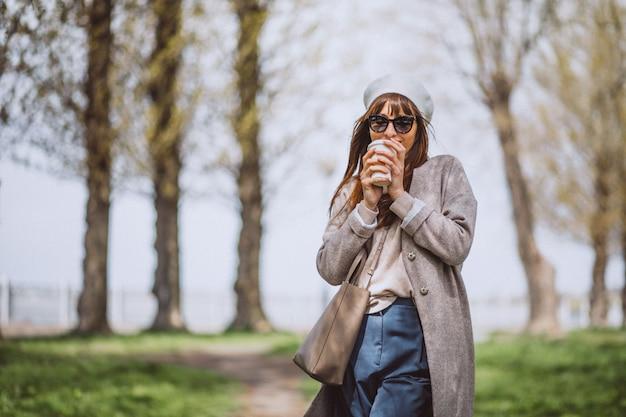 若い女性が公園でコーヒーを飲む 無料写真