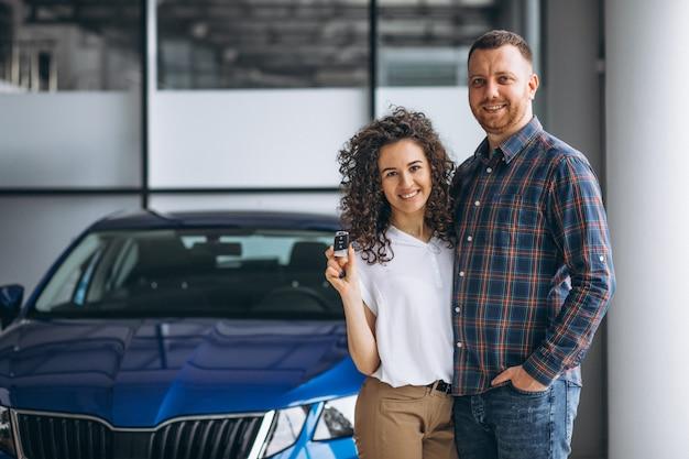 若い家族が車のショールームで車を買う 無料写真