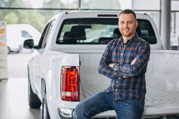 若い男が車のショールームで車を買う 無料写真