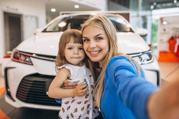 車の前に立っている彼女の小さな娘を持つ母 無料写真