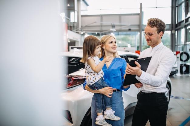車のショールームで営業担当者に話している娘を持つ母 無料写真