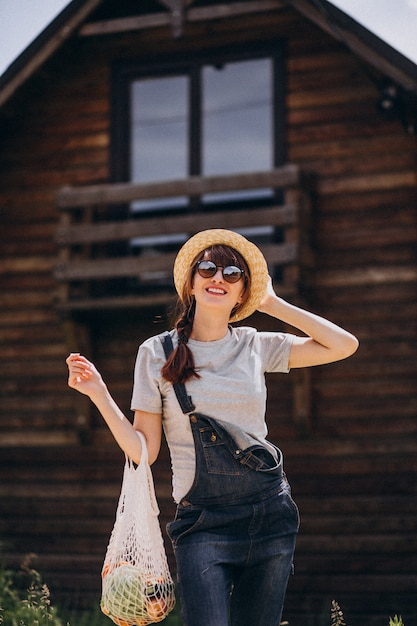 カントリーサイドのフルーツとエコバッグを持つ女性 無料写真