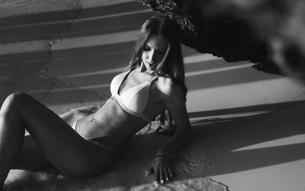 洞窟の下で海で横になっている水着でセクシーな女性 無料写真