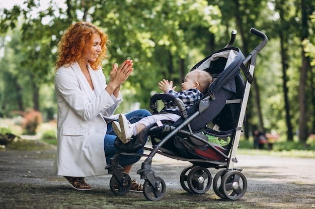 Мать с маленьким сыном в детской коляске в парке Бесплатные Фотографии