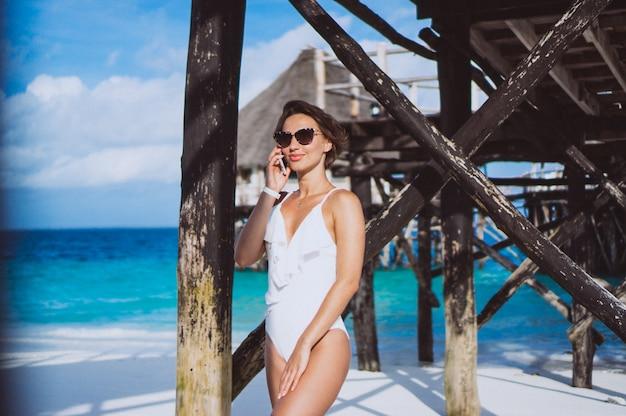 電話を使用して海沿いの白い水着の女性 無料写真
