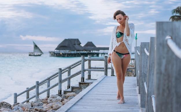 Красивая женщина в купальных костюмах на берегу океана Бесплатные Фотографии