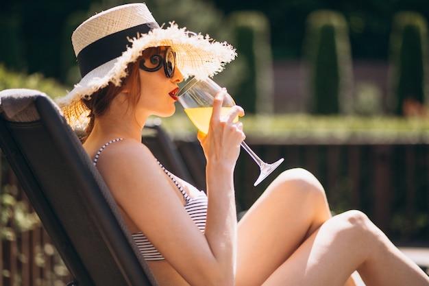 Женщина в купальнике на каникулах пьет сок Бесплатные Фотографии
