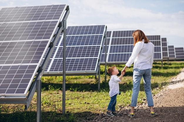 太陽電池パネルで彼女の幼い息子を持つ母 無料写真