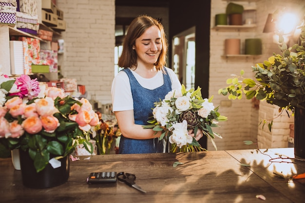 花の世話をして彼女自身の花屋で女性の花屋 無料写真