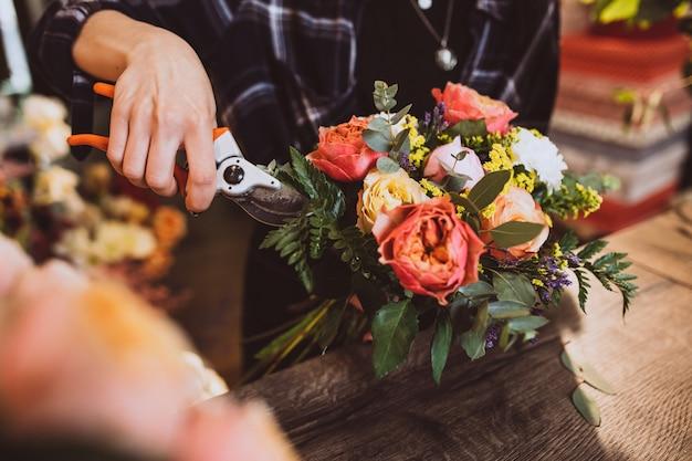 Женщина флорист в своем собственном цветочном магазине заботится о цветах Бесплатные Фотографии