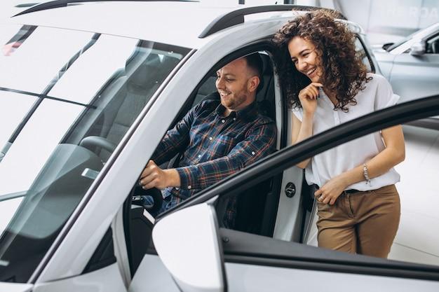 若い家族が車のショールームで車を選ぶ 無料写真
