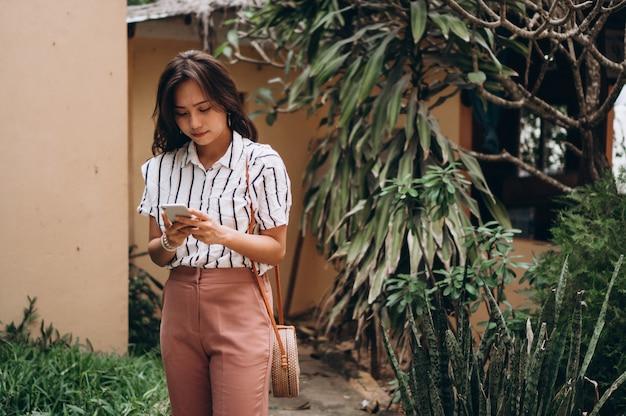 Азиатская бизнес-леди на каникулах говоря на телефоне Бесплатные Фотографии