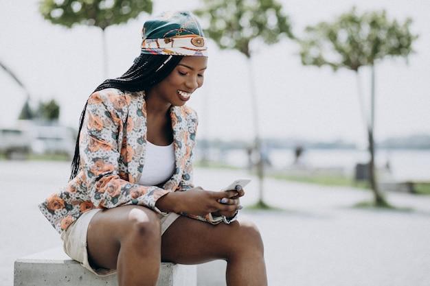 アフリカ系アメリカ人の女性が公園で座っていると電話を使用して 無料写真