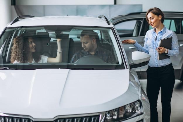若いカップルが車のショールームで車を選ぶ 無料写真