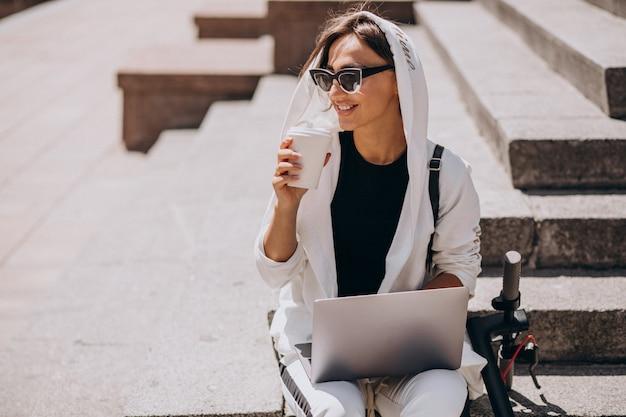 スクーターで階段に座ってラップトップを持つ若いビジネス女性 無料写真