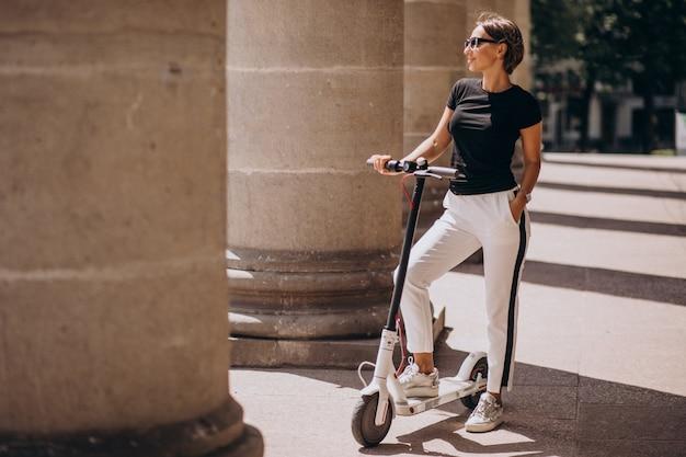 大学の建物で若い女性乗馬スコッター 無料写真
