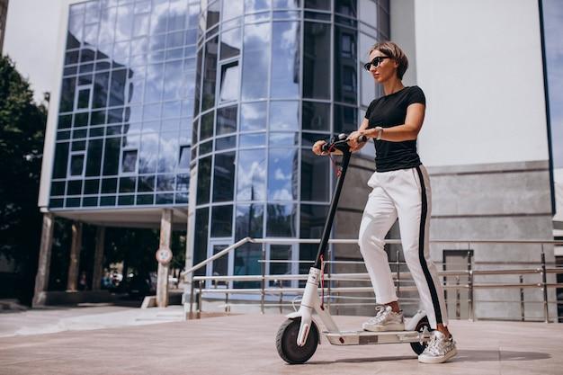 超高層ビルでスコッターに乗る若い女性 無料写真