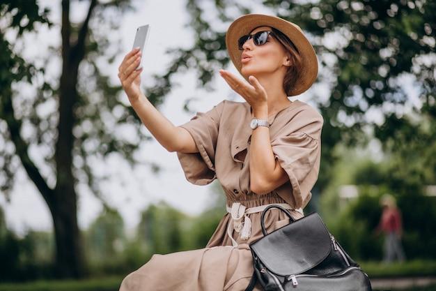 Парк молодой женщины сидя используя телефон Бесплатные Фотографии