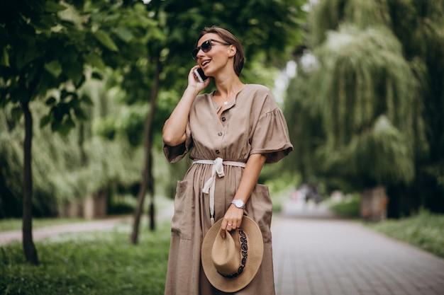 公園で携帯電話を持つ若い女性 無料写真