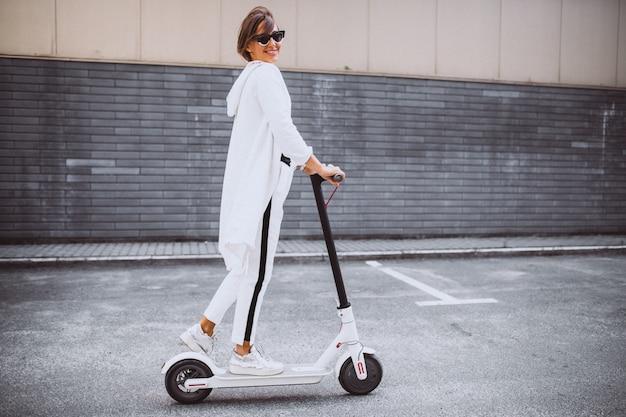 白い乗馬スクーターに身を包んだ若い女性 無料写真