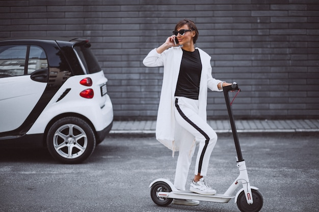 Молодая красивая женщина, одетая в белый скутер Бесплатные Фотографии