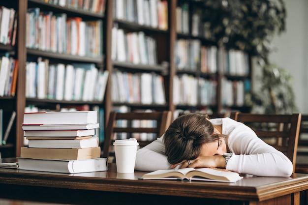 テーブルの上の図書館で寝ている学生 無料写真
