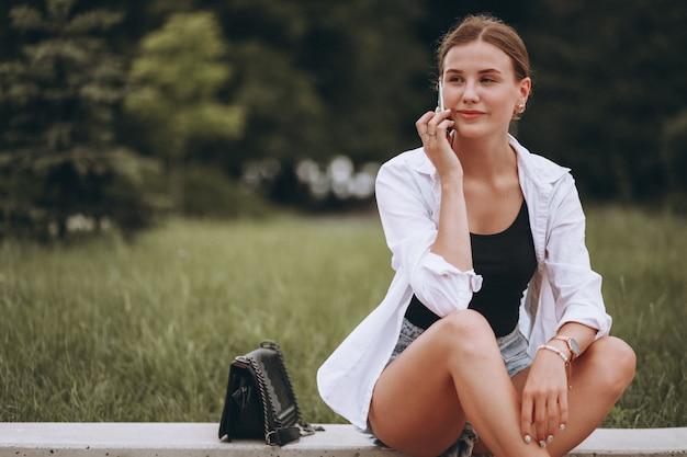Красивая девушка сидит на улице и с помощью телефона Бесплатные Фотографии