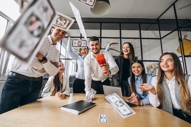 オフィスでお金を投げる人々のグループ 無料写真