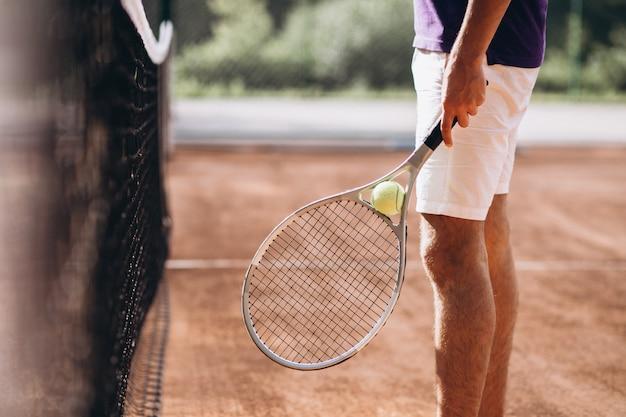 Молодой человек теннисист на корте, теннисная ракетка крупным планом Бесплатные Фотографии