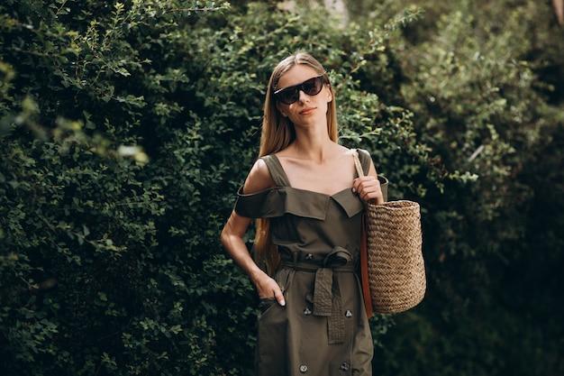 緑のブッシュの背景に公園に立っている若い女性 無料写真