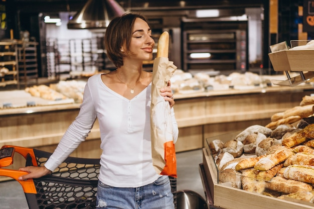 焼きたてのパンを買う食料品店の女性 無料写真