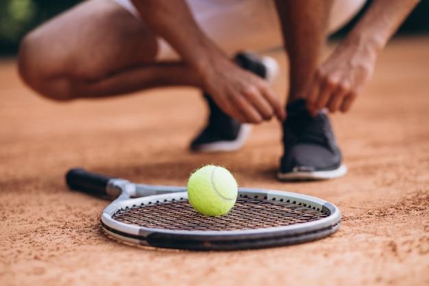 コートで若い男のテニス選手、テニスラケットをクローズアップ 無料写真