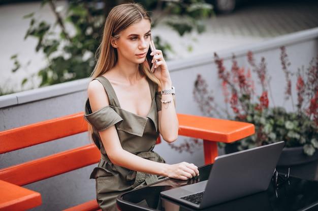 カフェで外のラップトップに取り組んでいる若いビジネス女性 無料写真