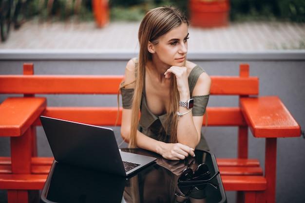 Молодая бизнес-леди работая на компьтер-книжке снаружи в кафе Бесплатные Фотографии