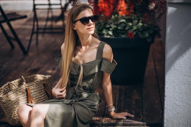 Молодая женщина, сидя за пределами кафе Бесплатные Фотографии