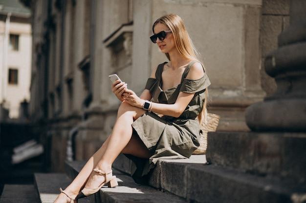 Молодая женщина сидит на лестнице и разговаривает по телефону Бесплатные Фотографии