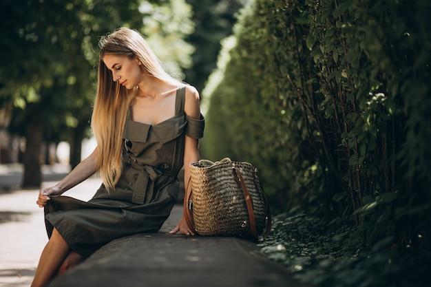 公園に座っている緑のドレスの若い女性 無料写真