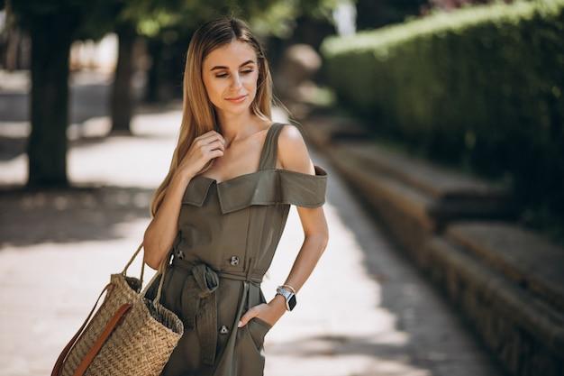 公園の外の緑のドレスの若い女性 無料写真
