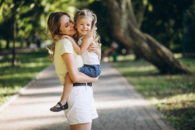 公園を歩いて小さな娘を持つ若い女性 無料写真