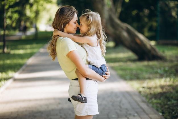 Молодая женщина с маленькой дочерью гуляя в парк Бесплатные Фотографии