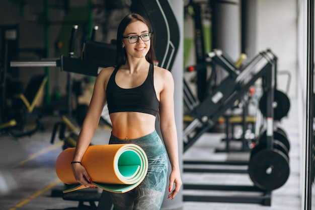 Женщина в тренажерном зале с ковриком для йоги Бесплатные Фотографии