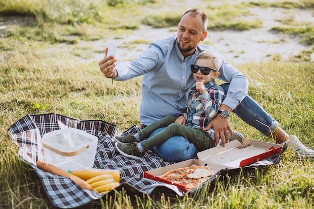 公園でピクニックを持つ息子を持つ父 無料写真