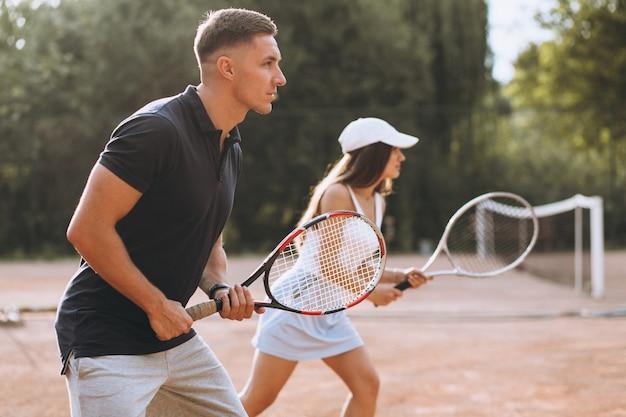 コートでテニスをしている若いカップル 無料写真