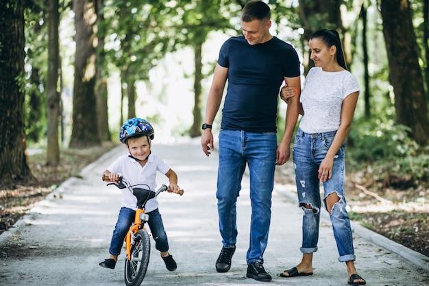 Отец с матерью учат своего маленького сына кататься на велосипеде Бесплатные Фотографии