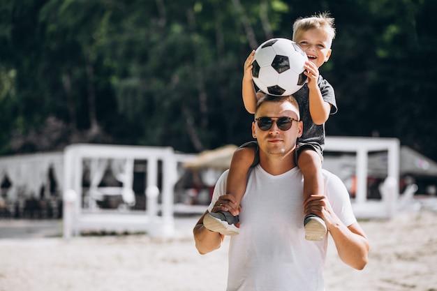 ビーチでサッカーの息子と父 無料写真