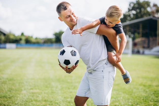 Отец с сыном играют в футбол на поле Бесплатные Фотографии