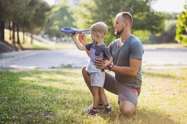 Отец с сыном, играя с игрушечным самолетом в парке Бесплатные Фотографии