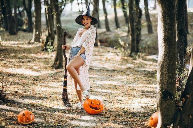 森のハロウィーンのほうきでウィッチ帽子に身を包んだ若い女性 無料写真