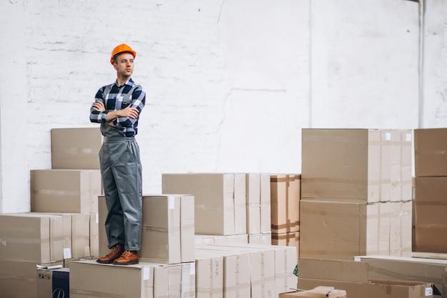 Молодой человек работает на складе с ящиками Бесплатные Фотографии